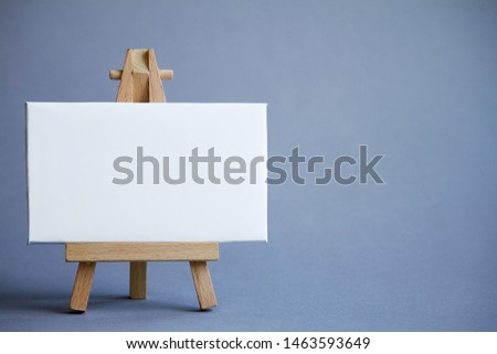 Miniature easel with a white board for writing, pointer on white surface, concept of direction and graphics, selective focus #1463593649