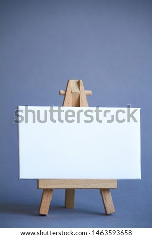 Miniature easel with a white board for writing, pointer on white surface, concept of direction and graphics, selective focus #1463593658