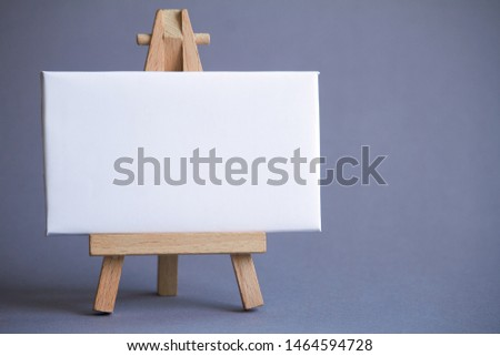 Miniature easel with a white board for writing, pointer on white surface, concept of direction and graphics, selective focus #1464594728