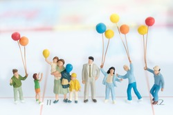 Miniature family with balloon using as background family day concept.