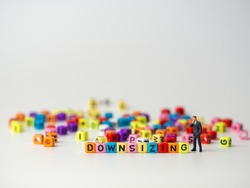 miniature figure businessman in dark blue suit standing backside of colorful of downsizing alphabet and thinking about how to Reduce trade, spend and downsizing Organization.