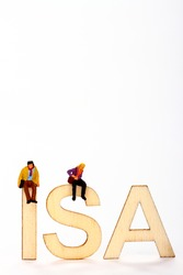 Miniature figure couple sat on wooden ISA letters individual tax free savings account concept with space for copy