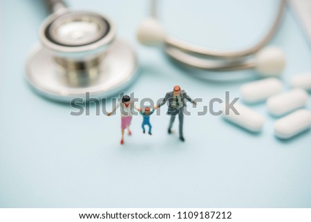 miniature figure family stand with stethoscope and pills on blue  background.health and relationship concept