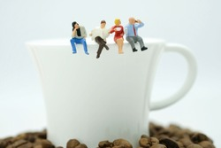 Miniature figure : Group of people sitting on the white mug drinking coffee , reading newspaper use as relaxing time.