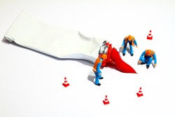 Miniature figure people investigating an artists red paint tube spillage