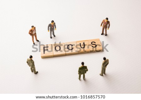 Miniature figures businessman : meeting on focus word by wooden block letters on white paper background, in concept of business and corporation #1016857570