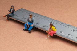 Miniature figures sit on a metal rule or ruler demonstrating the concept of social distancing to avoid transmission of the corona virus or other contagious illness