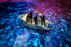 Miniature figurine businessmen ride on dollar bill origami yacht
