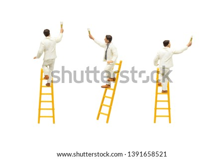 Miniature figurine character as painter standing on wooden ladder and painting wall with paint tools isolated on white background. Foto stock ©
