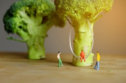 Miniature figurine character: 1 people sitting on swing that hanging on broccoli and 2 people standing on wooden floor near by for chatting