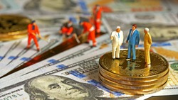 Miniature figurine : Financial Business Group standing on bitcoin and Workers are digging dollar Creating wealth for the capitalists. Digital Money and Bitcoin, Success, dealing and partner concept.