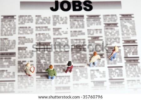 miniature figurine of people standing in front of jobs  seeking offerings