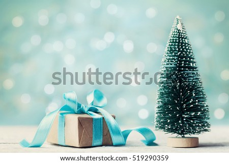 Miniature fir tree and christmas gift box against blue bokeh background. Holiday greeting card. #519290359