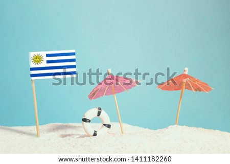 Miniature flag of Uruguay on beach with colorful umbrellas and life preserver. Travel concept, summer theme. #1411182260
