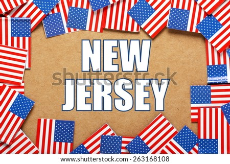 Miniature flags of the United States of America form a border on brown card around the name of the state of New Jersey