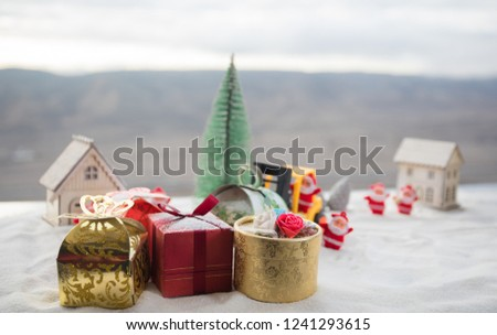 Photo of Miniature Gift Box by Forklift Machine on snow ,Determined Image for Christmas Holiday and Happy New Year Gift Celebration concept. Selective focus