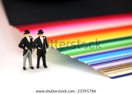 Miniature homosexual couple in tuxedos standing next to rainbow colored paper. Gay/same sex marriage concept.
