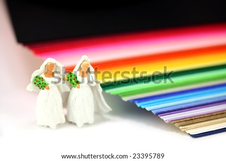 Miniature homosexual couple in wedding dresses standing next to rainbow colored paper. Gay/same sex marriage concept.
