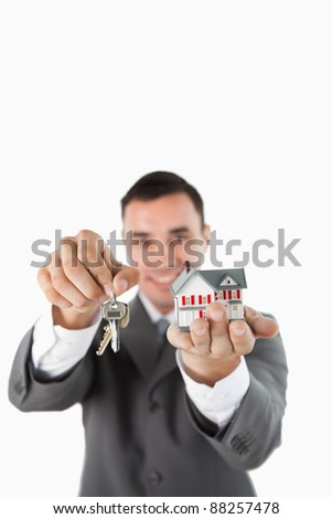 Miniature house and keys being presented by male estate agent against a white background