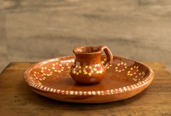 Miniature jar and traditional clay mexican plate hand painted with floral pattern flowers on an old wooden surface against a blurry rocky background in a kitchen