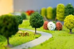 miniature landscape of a park with trees a small  road and grass. Selective focus.