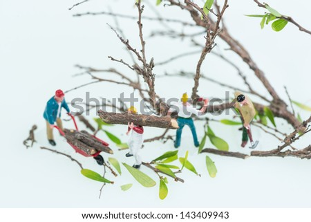 Miniature lumberjacks felling trees and carrying logs top view close up