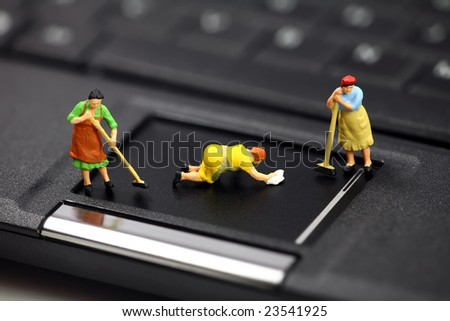 Miniature maids or cleaning women on a laptop computer. They are cleaning viruses, spyware and trojans. Computer anti-virus and security concept.