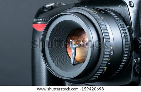 Miniature man cleaning camera lens. Macro photo