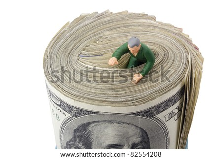 Miniature man drowning in a roll of American money.