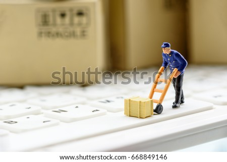Miniature messenger in a blue dress with a crate or wooden box on a white keyboard. Concept of delivery parcel to customers who ordered / bought things or goods from online stores by using internet.