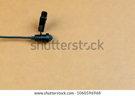 Miniature microphone of the buttonhole. A small microphone for recording quality sound on a brown background. Lavalier microphone