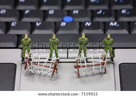 Miniature military soldiers and barbed wire are guarding a laptop from viruses, spyware and identity thieves. Computer security concept.