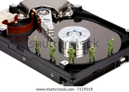 Miniature military soldiers are guarding a computer hard drive from viruses, spyware and identity thieves. Computer data security concept.