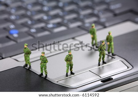 Miniature military soldiers are guarding a laptop from viruses, spyware and identity thieves. Computer security concept. - stock photo