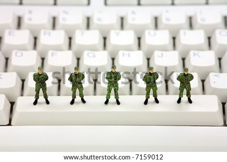 Miniature military soldiers are standing on a computer keyboard guarding it from viruses, spyware and identity thieves. Computer security concept.