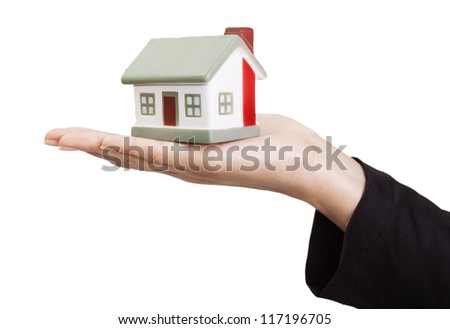 Miniature model concept house resting on a female hand