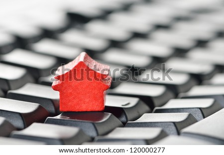 Miniature model home sitting on a computer keyboard. Web hosting or real estate on the internet concept.
