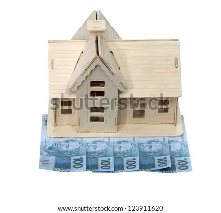 Miniature model house standing on a heap of dollar bills