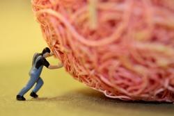 miniature of a man pushing a pink stone