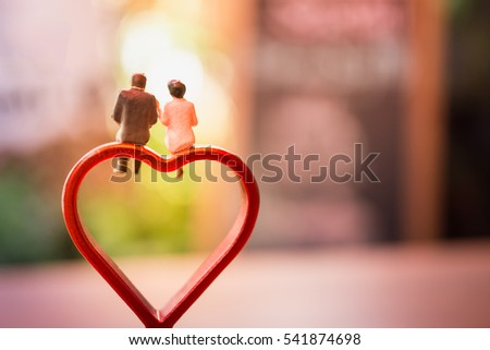 Photo of  Miniature of a women and a man in love sitting on heart sign bench with bokeh light copyspace, couple in love and pre-wedding background concept