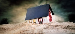 Miniature of house standing in pile of sand