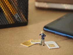 Miniature people and sim card on the table with blurred stationery stuff and handphone as a background. Technology and telecommunication business concept.