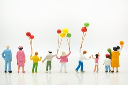 Miniature people: back view of happy family holding balloons with copy space using as background international family day, happy, love concept.