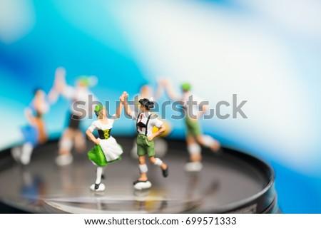 Miniature people.Bavarian man and girl in traditional Dirndl dresses are dancing having fun at the Oktoberfest in lens camera.Oktoberfest Munich in Germany.People dressed in traditional costumes.