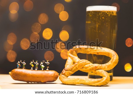 Miniature people.Bavarian man and girl in traditional Dirndl dresses are dancing having fun at the Oktoberfest in sausage and Glass of beer, pretzels background.Oktoberfest Munich in Germany.vintage.