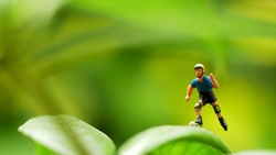 Miniature people: Boy playing on a natural background, green, with copy space using as education, Children's day concept.