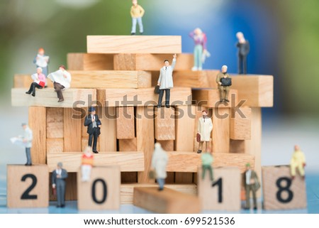 Miniature people: Business man standing on wood block using as background Choice of the best suited employee, HR, HRM, HRD, job recruiter concepts.