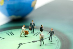 Miniature people : business man walking on the clock background, time business concept.