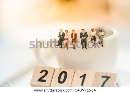 Miniature people : business team sitting on coffee cup and wooden number block 2017, for counting End of Year and Happy New year day celebration and Love background concept