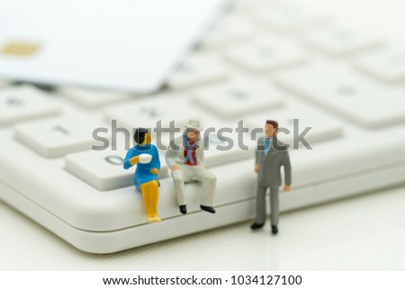 Miniature people: Business team standing and sitting on calculator using as background cost of business concept.